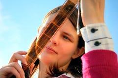 Mulher nova que olha a película Fotografia de Stock Royalty Free