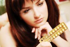 Mulher nova que olha seus comprimidos contraceptivos fotografia de stock