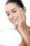Mulher nova que olha si mesma no sorriso do espelho Fotografia de Stock Royalty Free