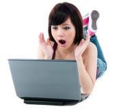 Mulher nova que olha surpreendida no portátil Fotografia de Stock