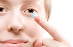 Mulher nova que põr a lente de contato azul foto de stock royalty free