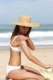 Mulher nova que põr o creme do sol sobre Foto de Stock Royalty Free