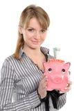 Mulher nova que põr o dinheiro no banco piggy fotografia de stock royalty free