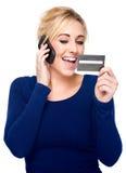 Mulher nova que paga pelo cartão de crédito e pelo telefone de pilha imagem de stock
