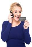 Mulher nova que paga pelo cartão de crédito e pelo telefone de pilha imagem de stock royalty free