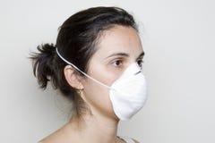 Mulher nova que põr sobre uma máscara de encontro à gripe dos suínos Imagens de Stock