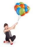Mulher nova que prende balões coloridos Foto de Stock