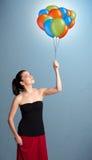 Mulher nova que prende balões coloridos Foto de Stock Royalty Free