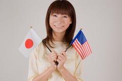 Mulher nova que prende a bandeira japonesa e o fla americano Fotos de Stock Royalty Free