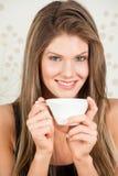 Mulher nova que prende um copo do chá e do sorriso Foto de Stock