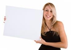Mulher nova que prende um sinal branco em branco Imagem de Stock