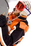 Mulher nova que prende um snowboard Foto de Stock Royalty Free