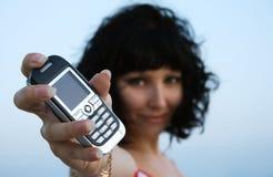 Mulher nova que prende um telefone móvel Fotografia de Stock