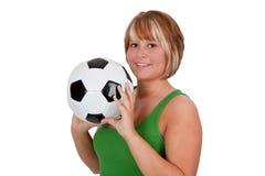Mulher nova que prende uma esfera de futebol Foto de Stock