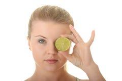 Mulher nova que prende uma fatia de limão imagem de stock