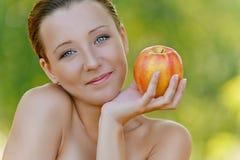 Mulher nova que prende uma maçã Imagens de Stock
