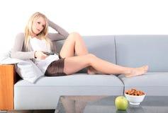 Mulher nova que presta atenção à tevê Foto de Stock