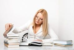 Mulher nova que procura alguma informação nos livros Imagens de Stock Royalty Free