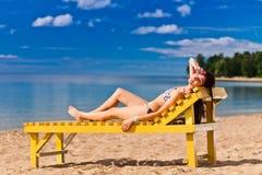 Mulher nova que relaxa na praia Fotografia de Stock Royalty Free