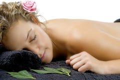 Mulher nova que relaxa na toalha preta Fotografia de Stock Royalty Free