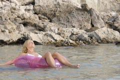 Mulher nova que relaxa no mar. Fotografia de Stock Royalty Free