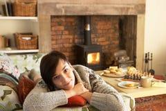 Mulher nova que relaxa pelo incêndio Imagens de Stock Royalty Free