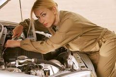 Mulher nova que repara o carro Fotografia de Stock Royalty Free