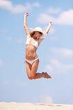 Mulher nova que salta em uma praia Imagens de Stock Royalty Free
