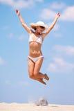 Mulher nova que salta em uma praia Fotos de Stock Royalty Free