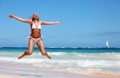 Mulher nova que salta na praia tropical Fotografia de Stock