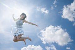 Mulher nova que salta no céu fotografia de stock royalty free