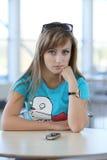 Mulher nova que senta no witn da tabela um telefone Foto de Stock Royalty Free