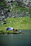 Mulher nova que senta-se ao lado do acampamento Fotografia de Stock Royalty Free