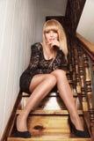 Mulher nova que senta-se em escadas Fotos de Stock
