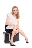 Mulher nova que senta-se em uma mala de viagem Fotos de Stock Royalty Free