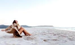 Mulher nova que senta-se na areia imagens de stock royalty free