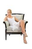 Mulher nova que senta-se na cadeira Fotografia de Stock Royalty Free