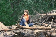 Mulher nova que senta-se na floresta Fotografia de Stock Royalty Free