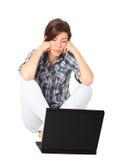 Mulher nova que senta-se na frente de seu portátil Fotografia de Stock
