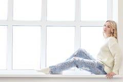 Mulher nova que senta-se na frente do indicador fotografia de stock
