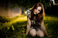 Mulher nova que senta-se na grama Fotos de Stock Royalty Free