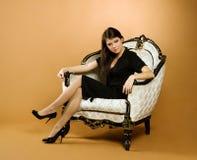 Mulher nova que senta-se na poltrona Foto de Stock