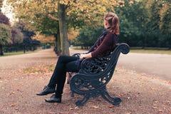 Mulher nova que senta-se no banco de parque Fotos de Stock