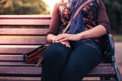 Mulher nova que senta-se no banco de parque Foto de Stock