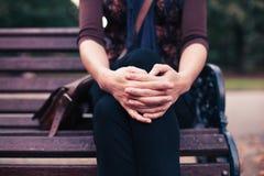 Mulher nova que senta-se no banco de parque Imagem de Stock Royalty Free