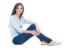 Mulher nova que senta-se no fundo branco Fotos de Stock Royalty Free