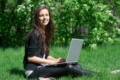 Mulher nova que senta-se no parque e que usa o portátil Fotos de Stock