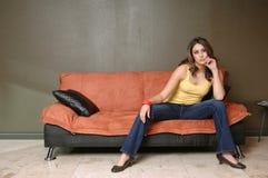 Mulher nova que senta-se no sofá imagens de stock royalty free