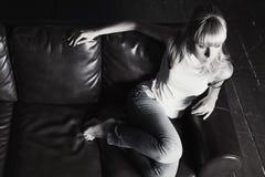 Mulher nova que senta-se no sofá fotos de stock