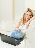 Mulher nova que senta-se no sofá com portátil Fotografia de Stock